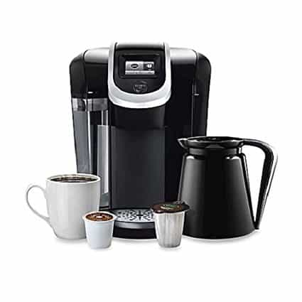 the keurig k350 with a pitcher, a mug, and two pods